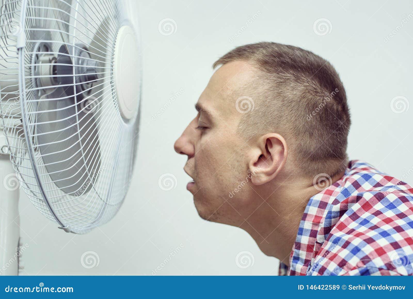Человек со стерней на его стороне страдает от жары и попытки охладить около вентилятора