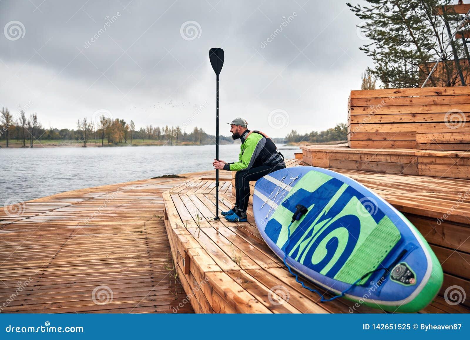 Человек со стойки paddleboard вверх