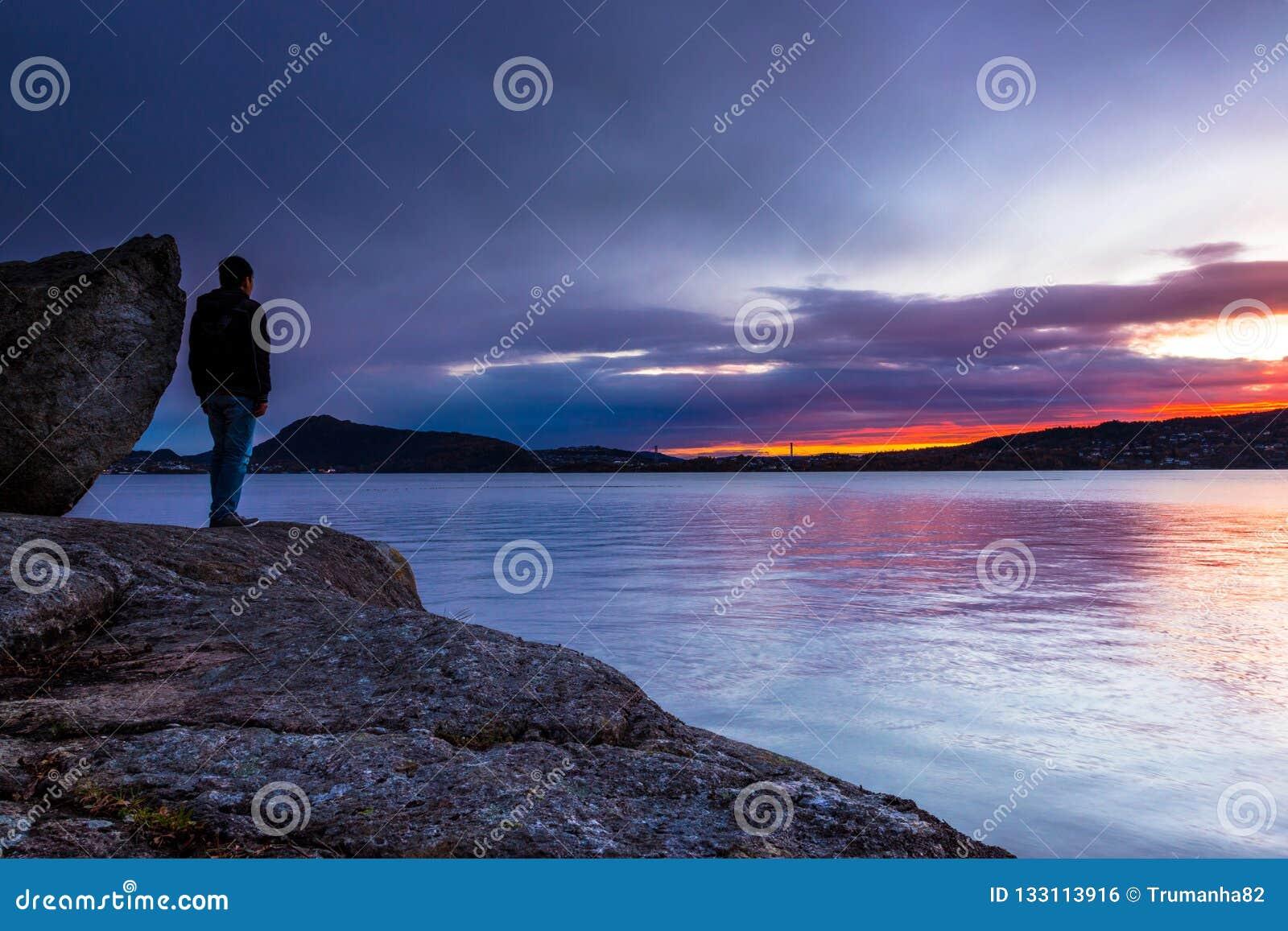 Человек стоя самостоятельно с его Thoughs на красочном Suset