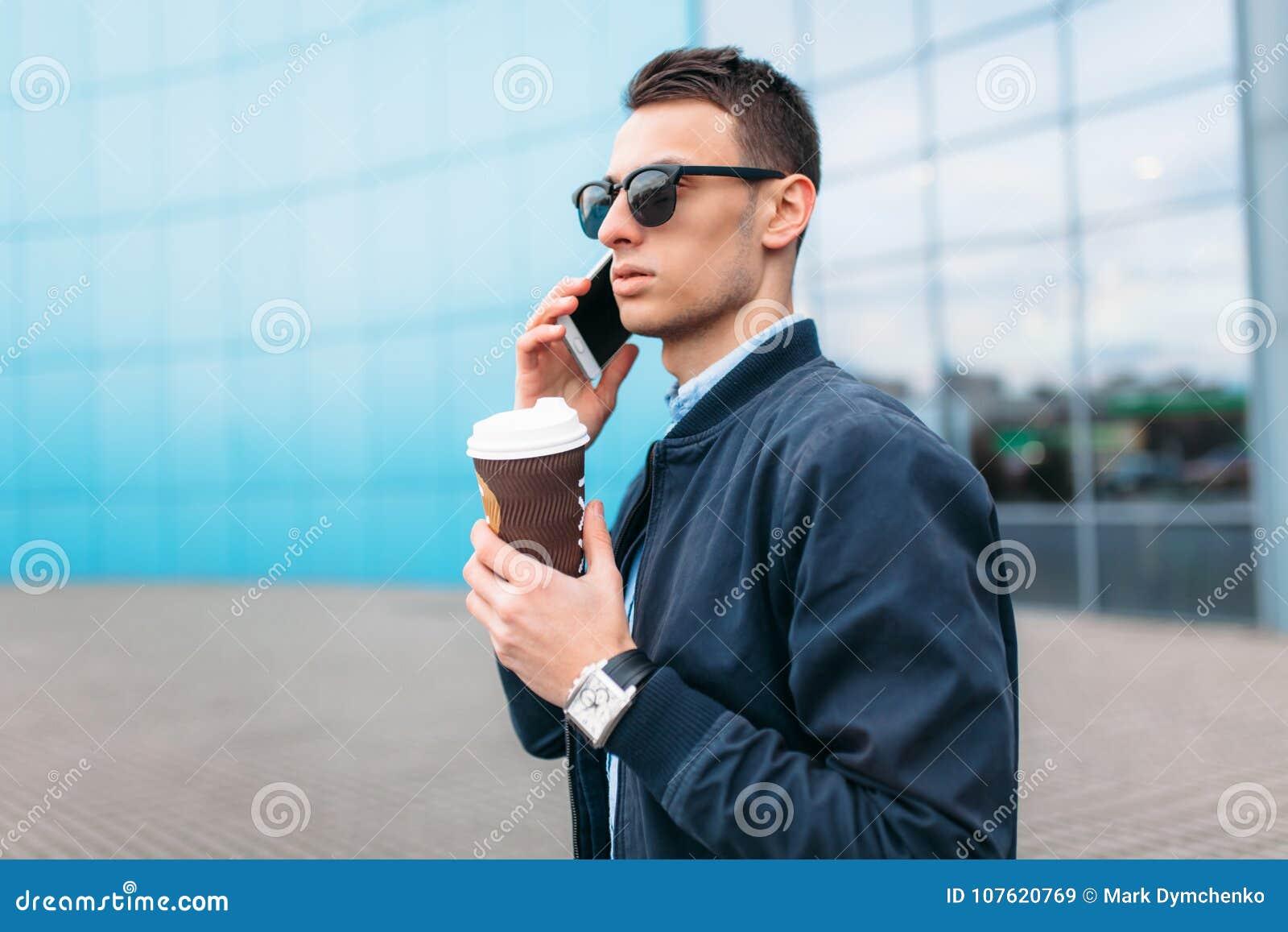 Человек с бумажным стаканчиком кофе, идет через город, красивый парня в стильных одеждах и солнечные очки, звоня телефонный звоно