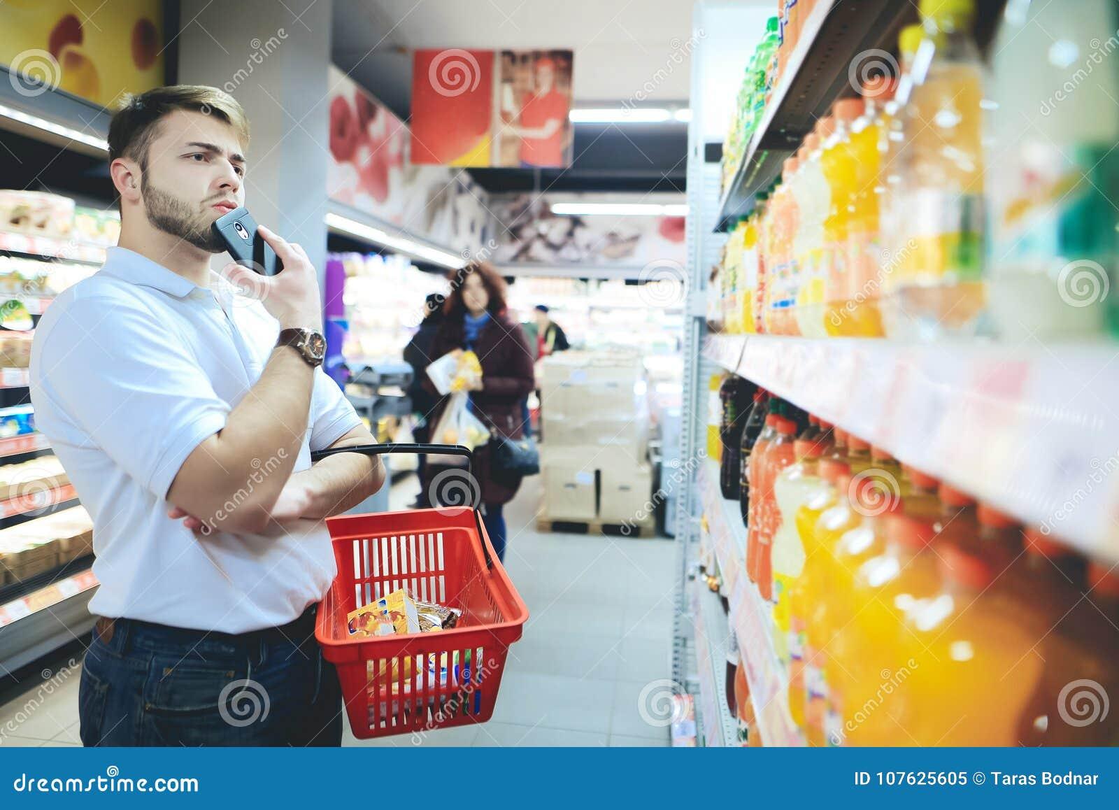 Человек с корзиной в его руках смотрит пить на супермаркете Человек с бородой покупает еду в супермаркете