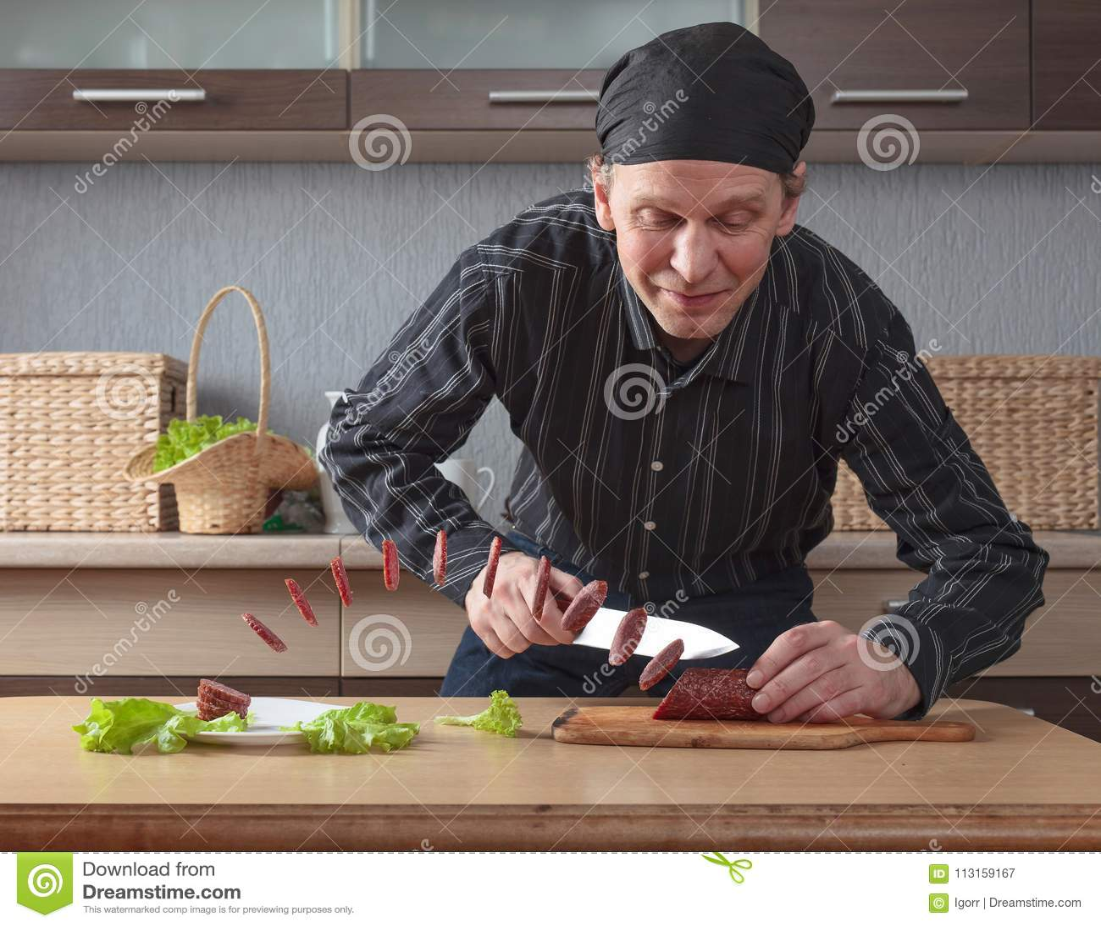 Человек с ножом режет сосиску частей