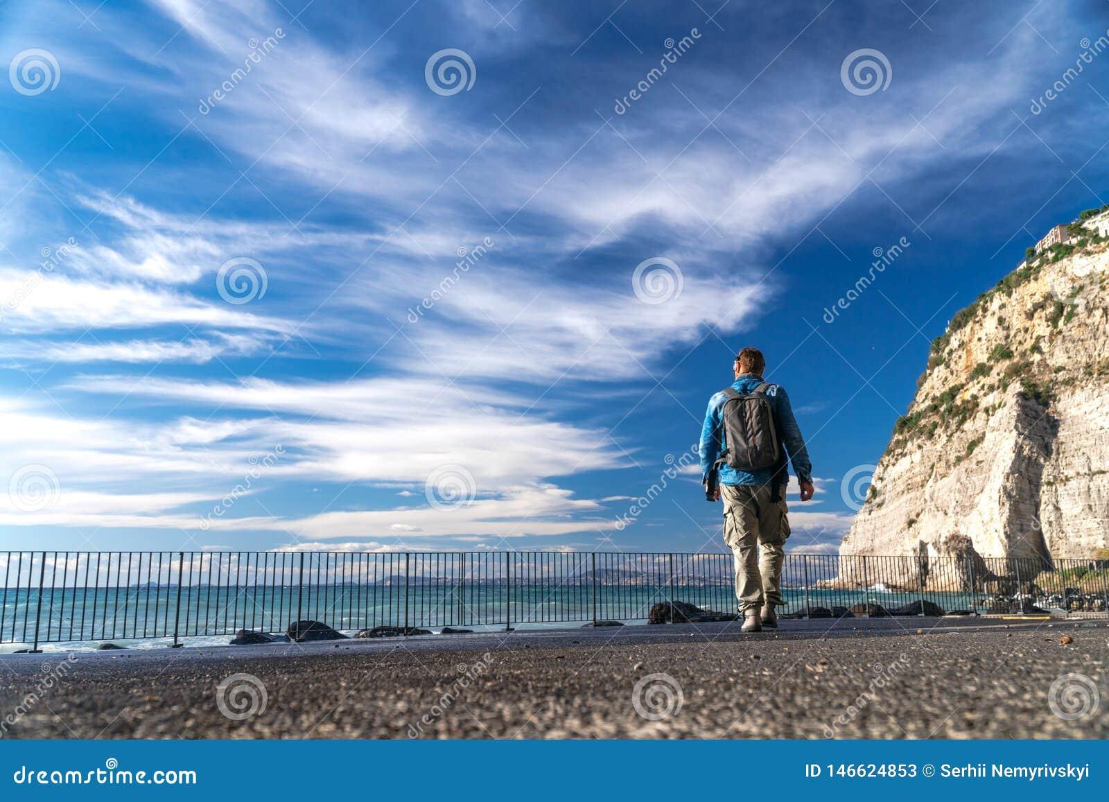 Человек с прогулкой рюкзака одной и наблюдая на bacground волн, облаков и гор воды сильном, Сорренто Италии
