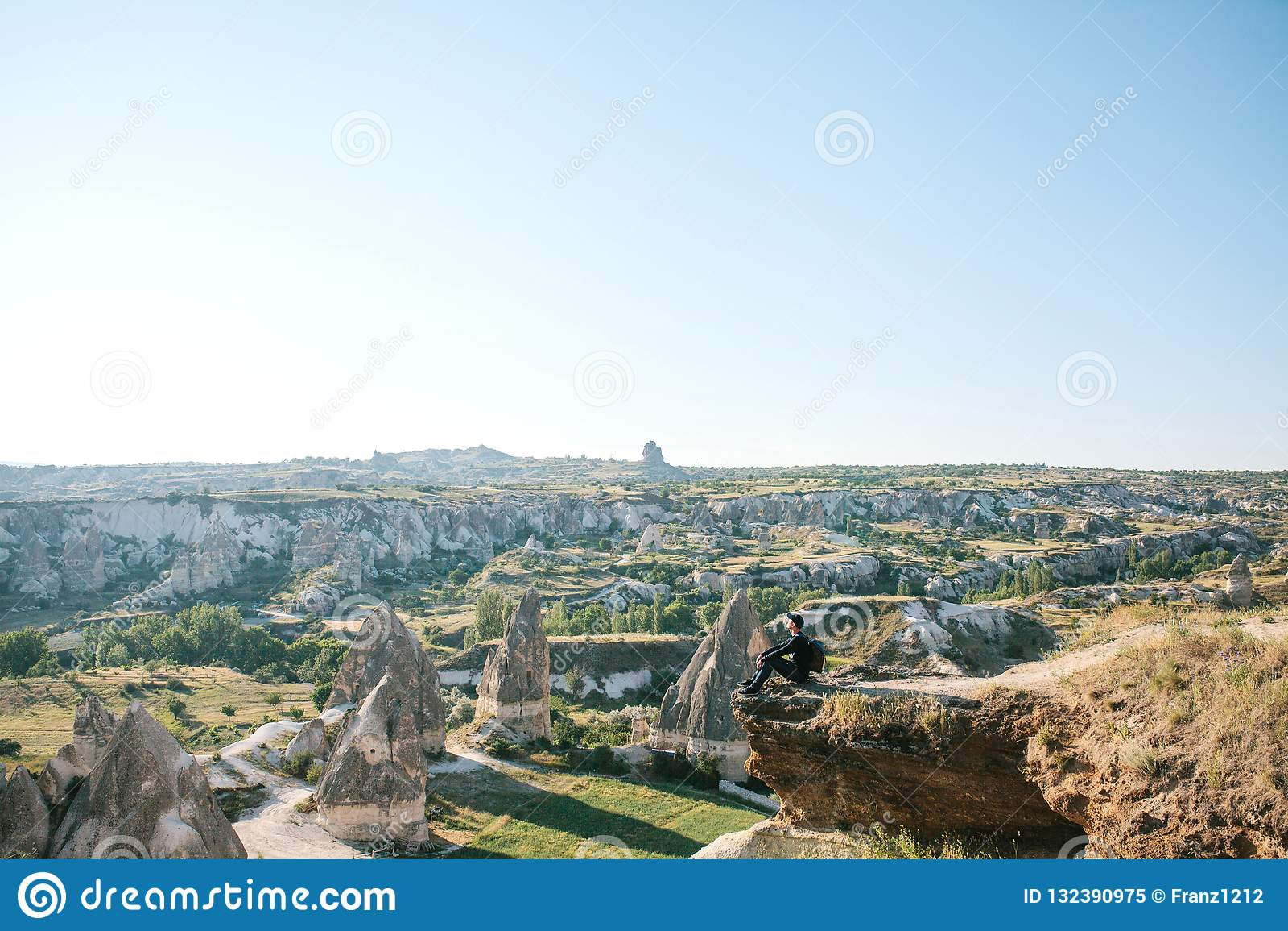 Человек с рюкзаком сидит поверх холма в Cappadocia в Турции