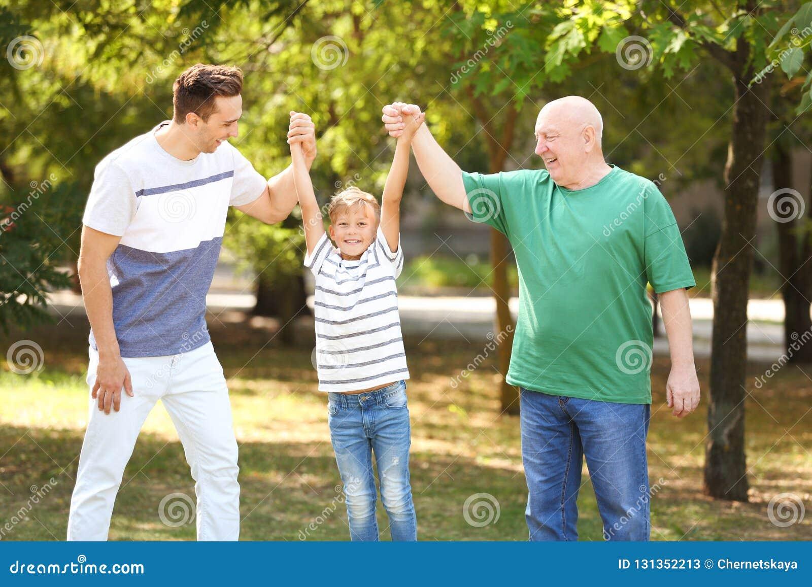 Человек с сыном и пожилым отцом в парке