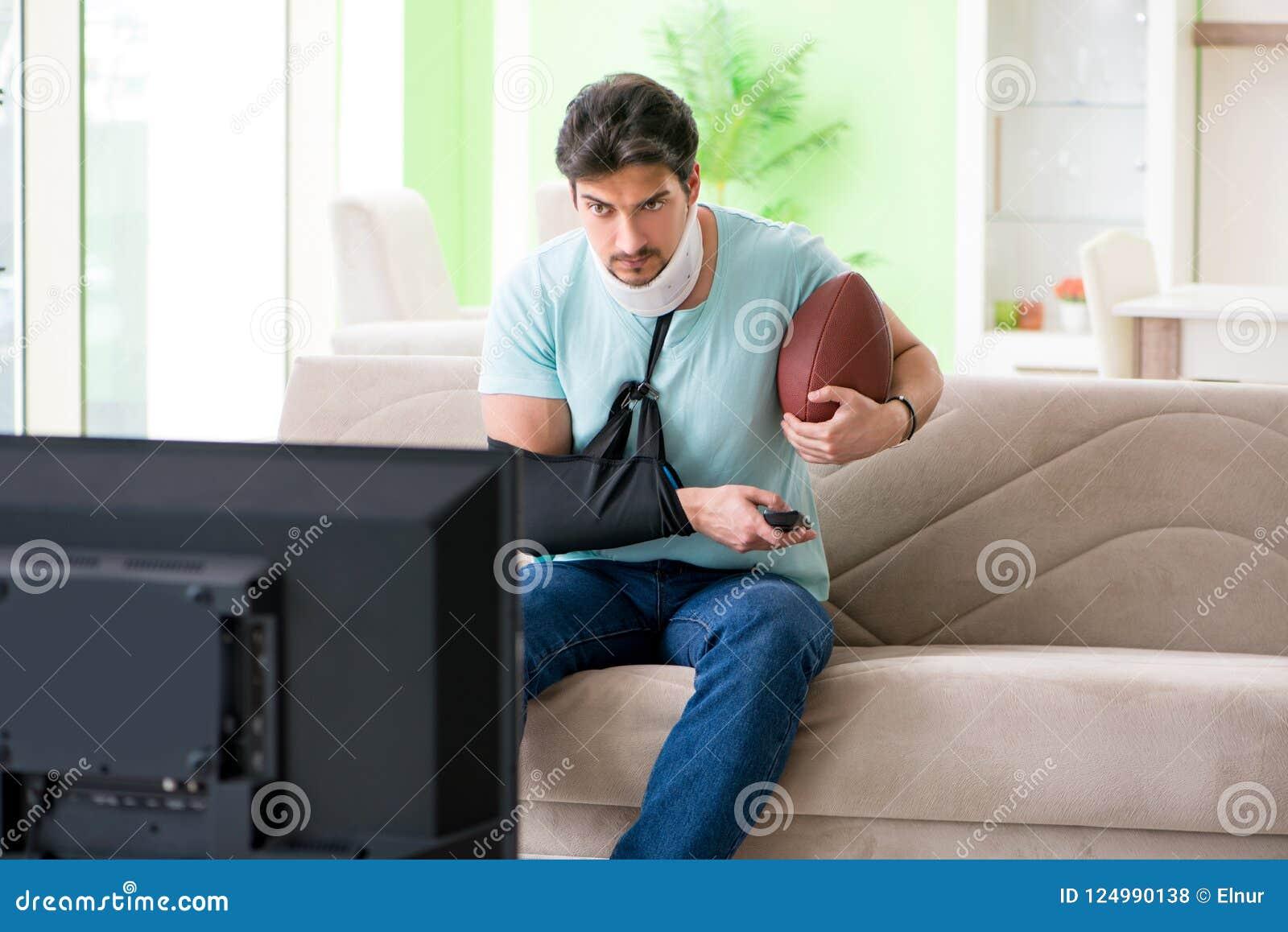 Человек с ушибом шеи и руки смотря американский футбол на ТВ