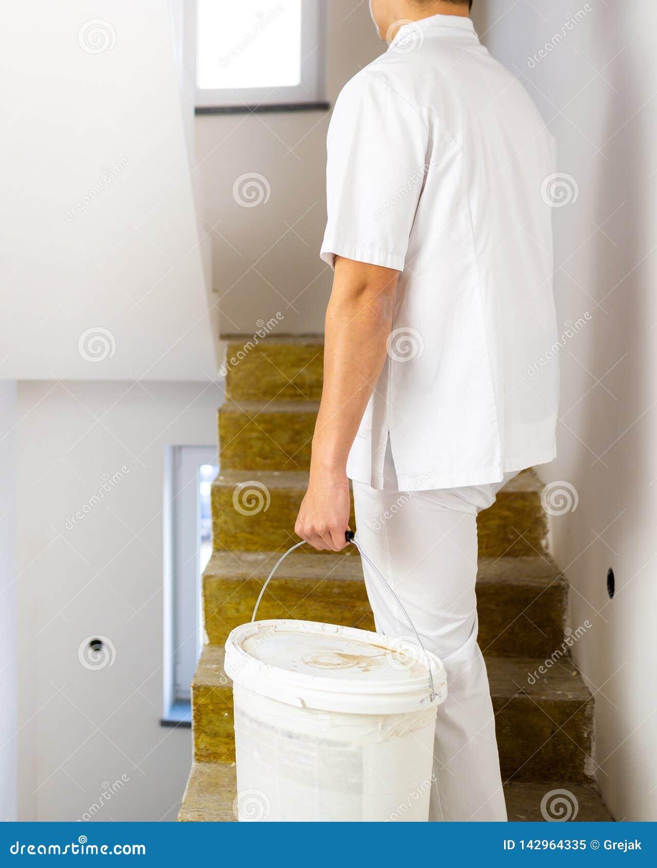 Человек художника работая в стенах картины дома белых