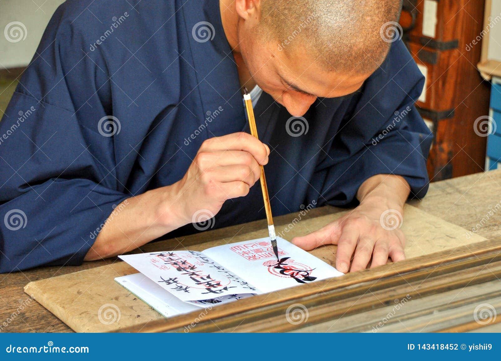 Человек Shinshoku писать печать Shuin для worshippers