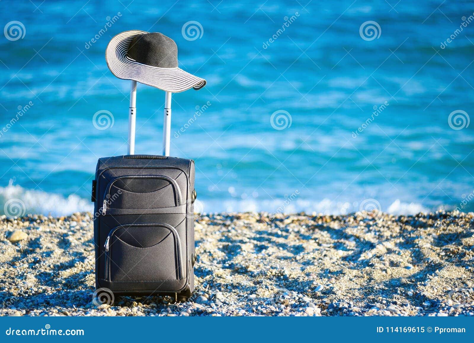 Чемодан и шляпа на пляже