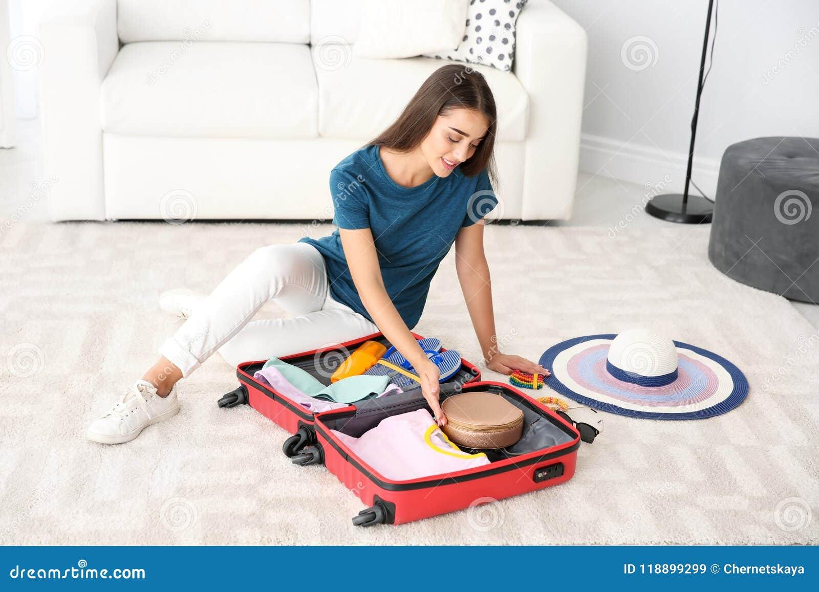 Чемодан упаковки молодой женщины дома