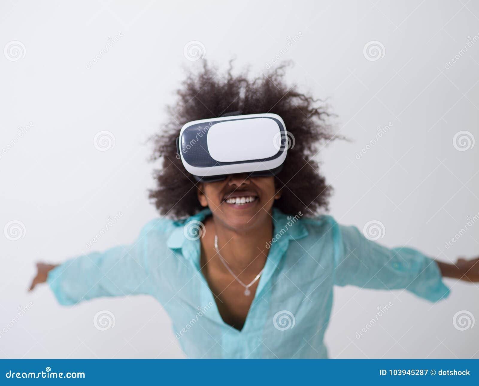 Черная девушка используя стекла шлемофона VR виртуальной реальности