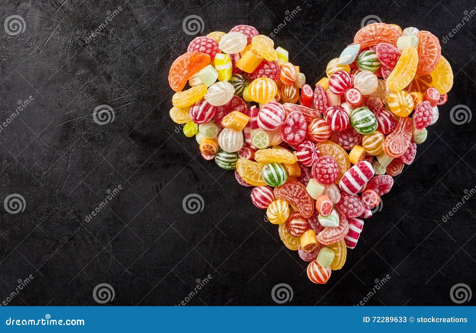 Черная предпосылка при форма сердца сделанная из конфет