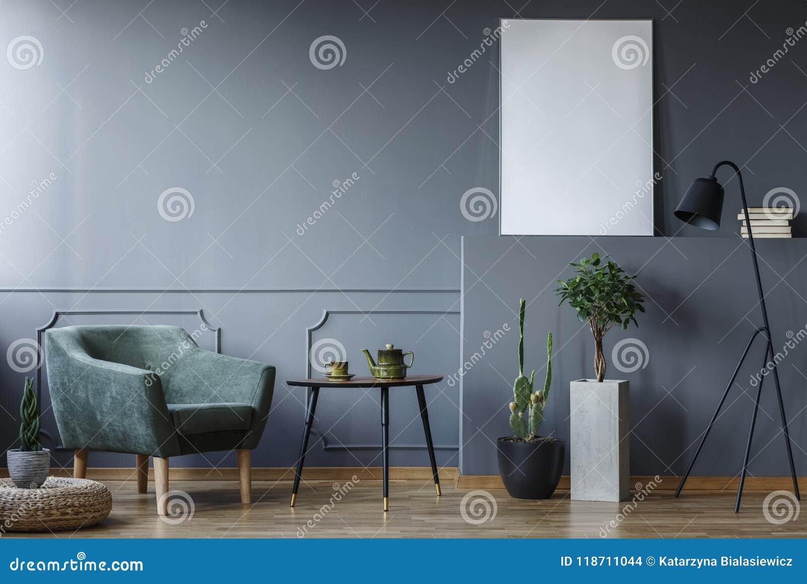 Черная таблица между зелеными креслом и заводами в сером интерьере w