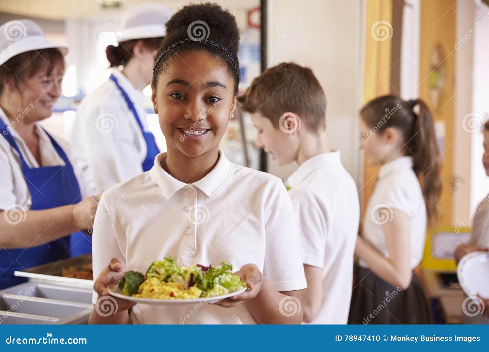 Черная школьница держит плиту еды в школьном кафетерии