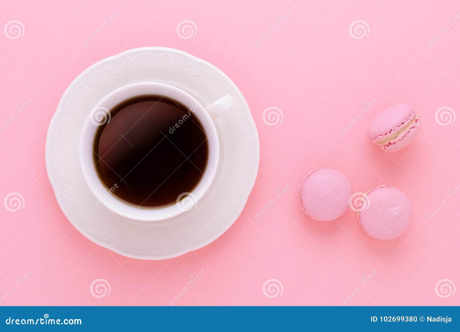 Чернота кофейной чашки с handmade macaroons на розовой предпосылке сверху