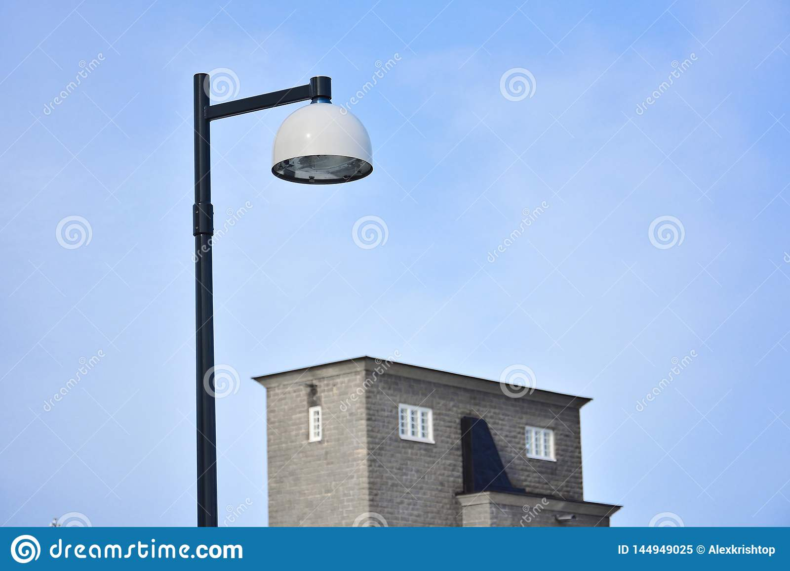 Черно-белая лампа металла и здание против предпосылки голубого неба