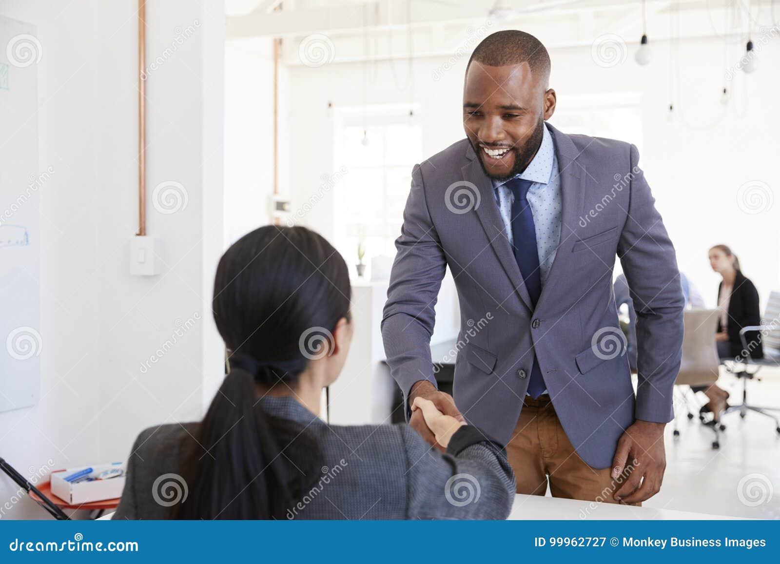 Черный бизнесмен и усаженная женщина тряся руки в офисе