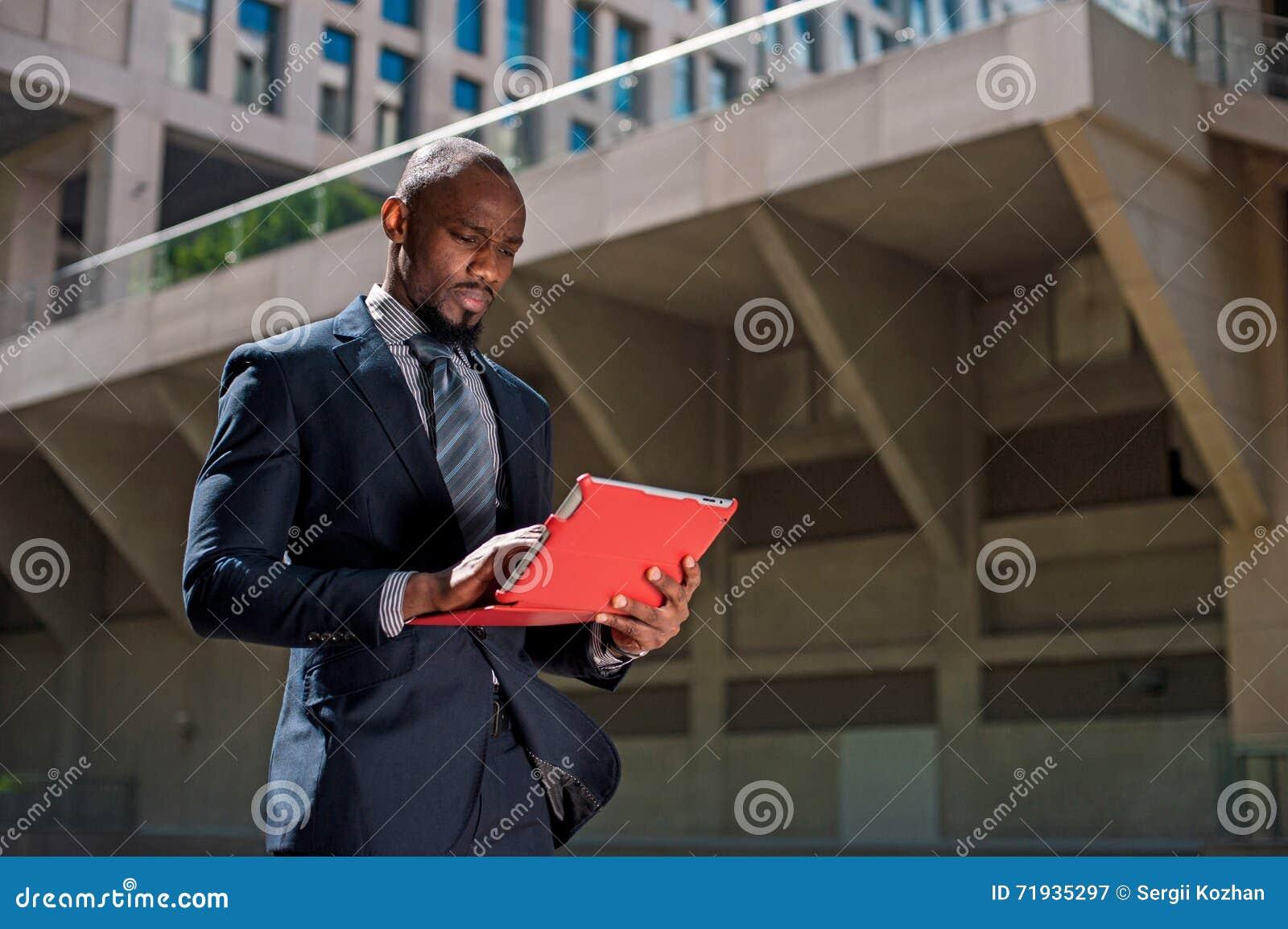Черный бизнесмен смотря его планшет в городском backgr