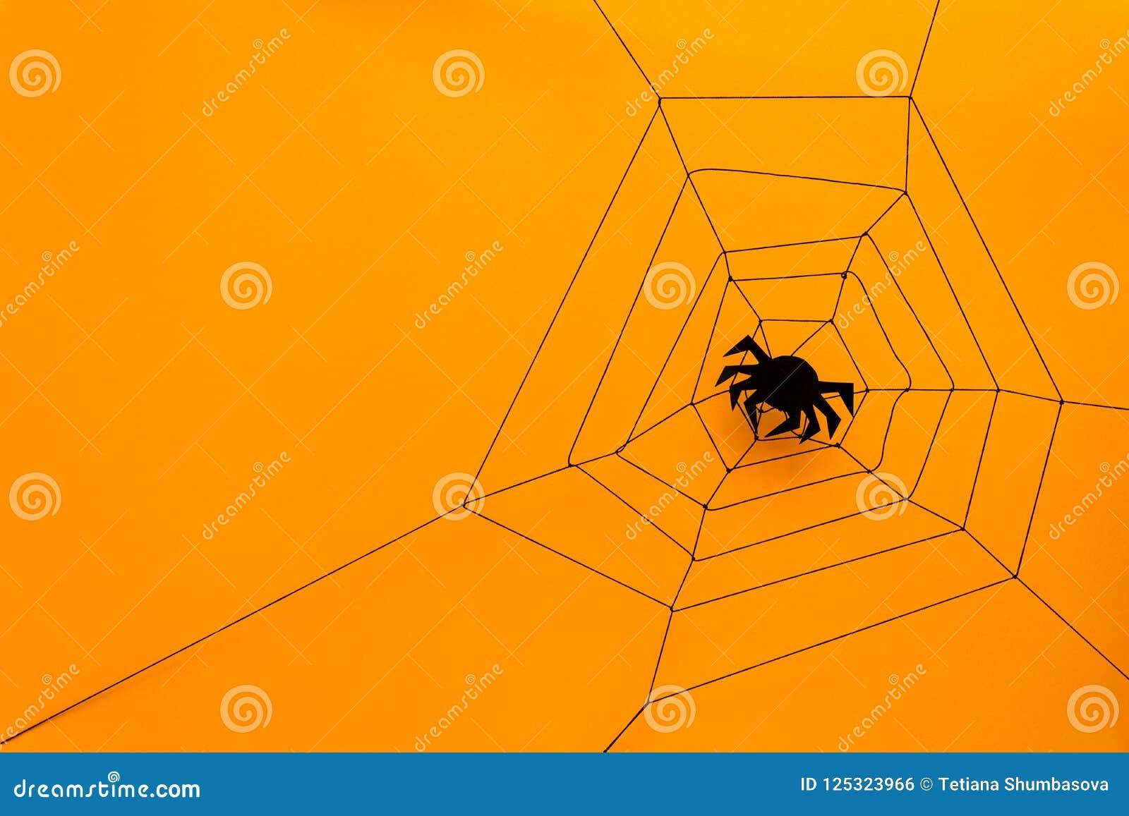 Черный бумажный паук с сетью на желтой предпосылке удерживания halloween даты принципиальной схемы календара жнец мрачного счастл