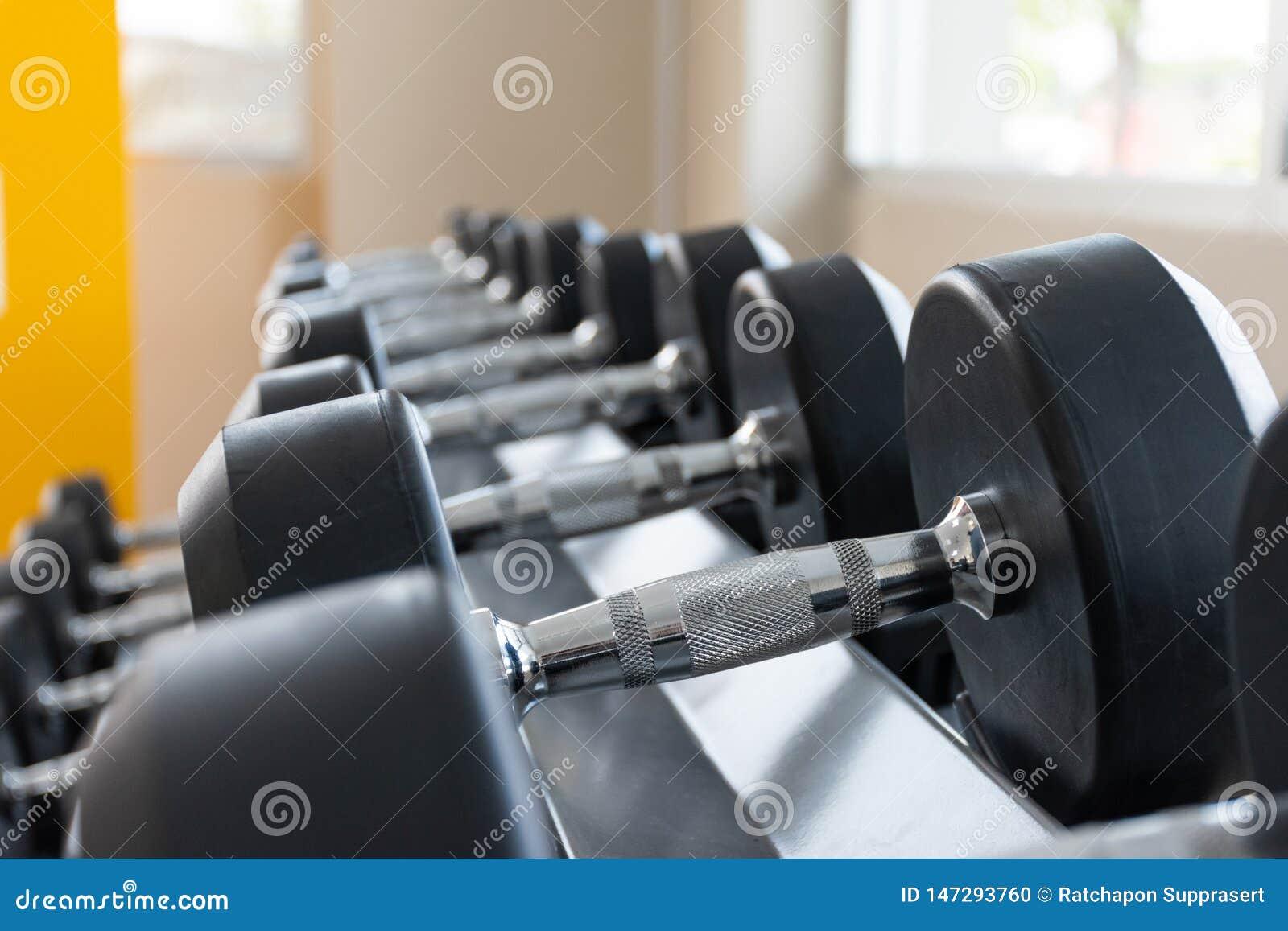 Черный набор гантели на конце шкафа вверх в концепции тренажера веса фитнес-центра спорта