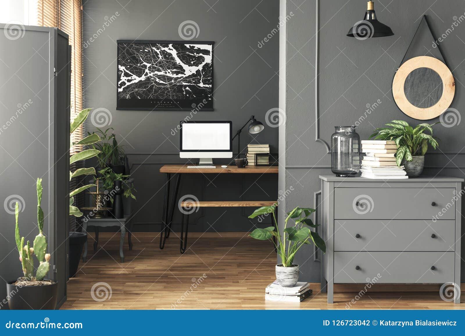 Черный плакат на серой стене над столом с модель-макетом в интерьере домашнего офиса с зеркалом Реальное фото