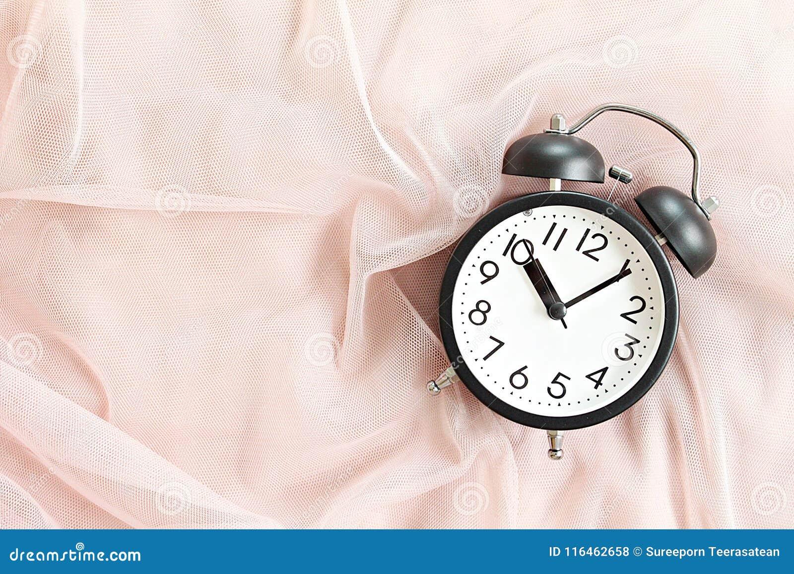 Черный ретро будильник на кровати в утре, взгляд сверху или плоском положении с космосом экземпляра готовым для добавлять или нас