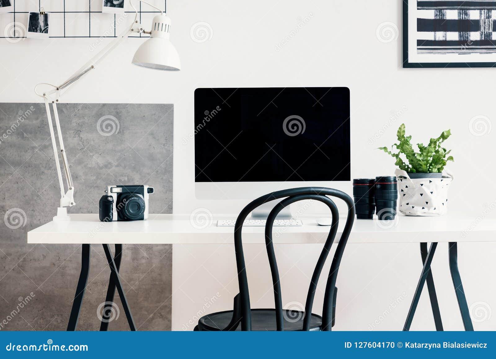 Черный стул белым столом с компьютером и лампой в современном интерьере домашнего офиса для профессионального фрилансера фотограф