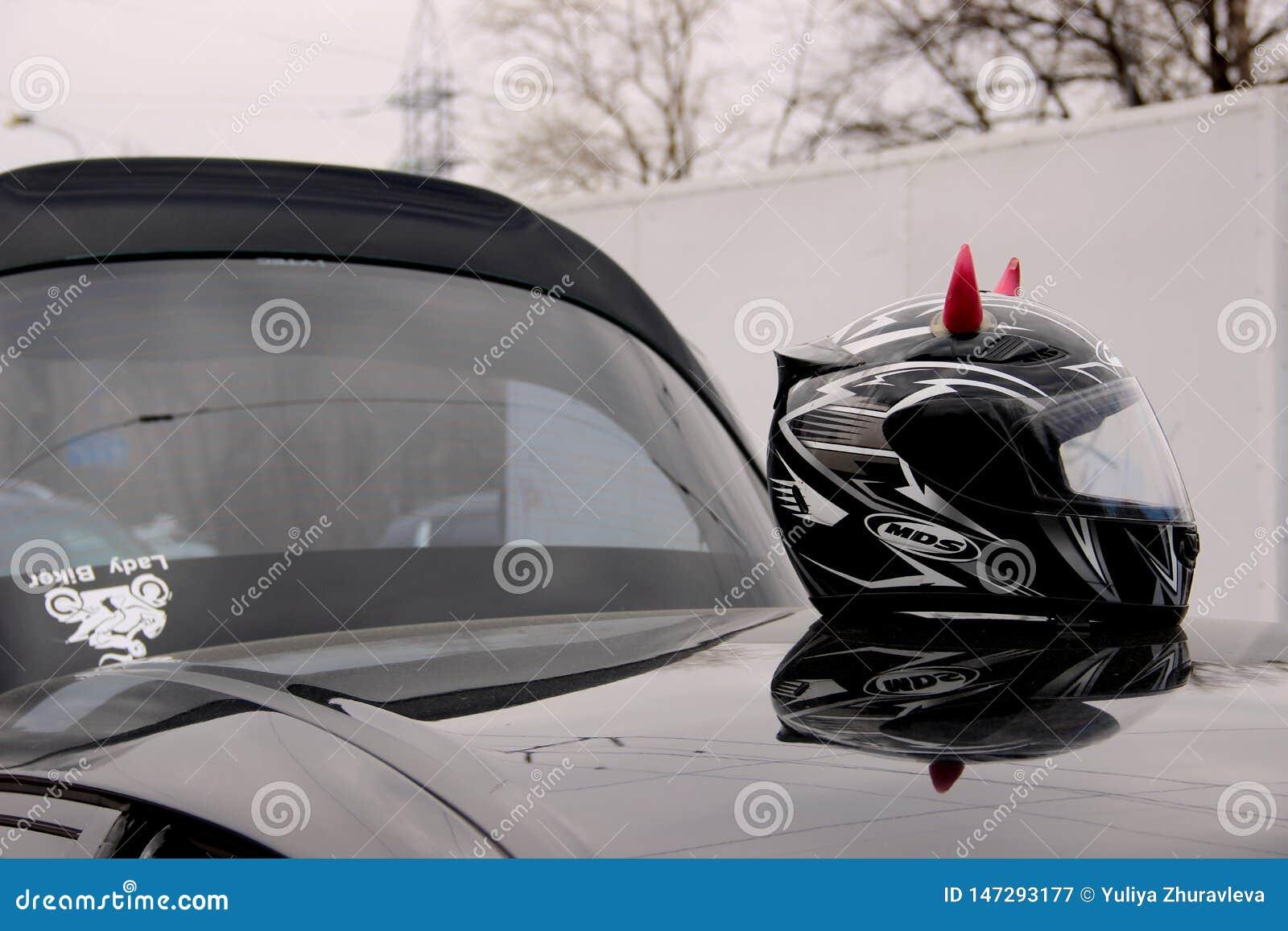 Черный шлем мотоцикла с розовыми рожками на крыше автомобиля со стикером велосипеда дамы