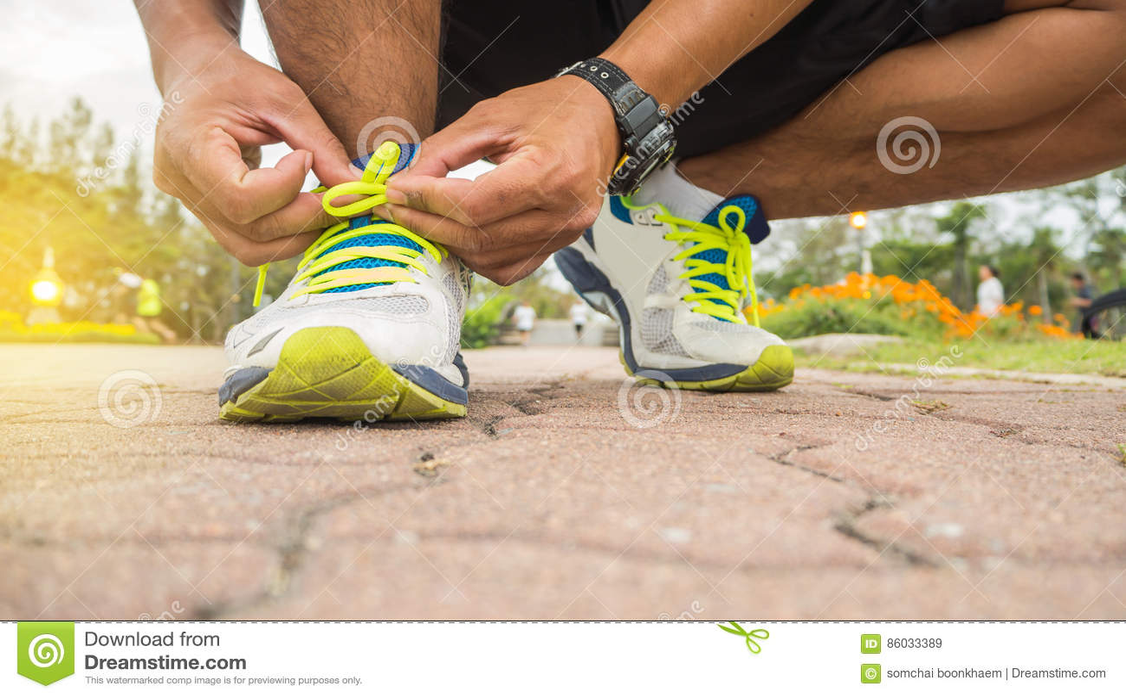 Человек бегуна связывая шнурки ботинок хода получая готовый для гонки