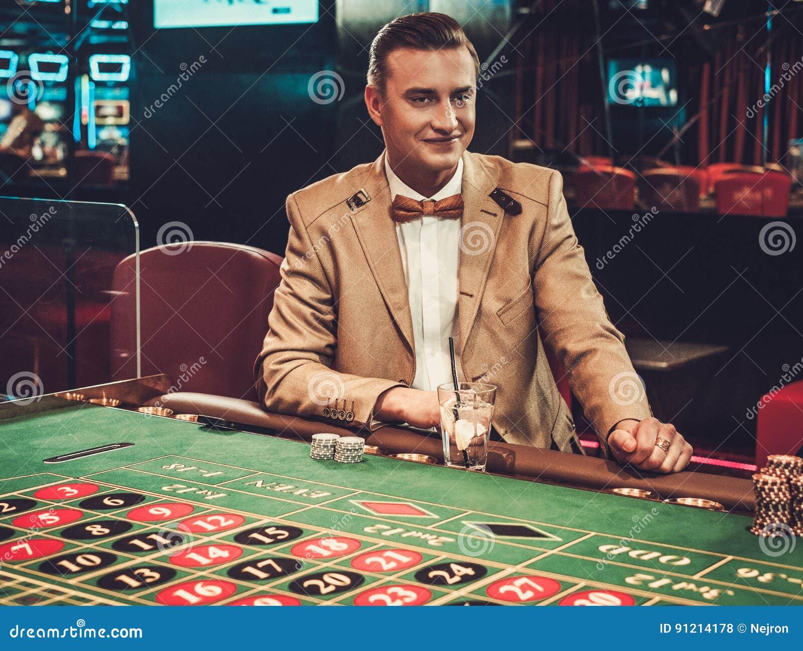 Человек высшего класса играя в азартные игры в казино