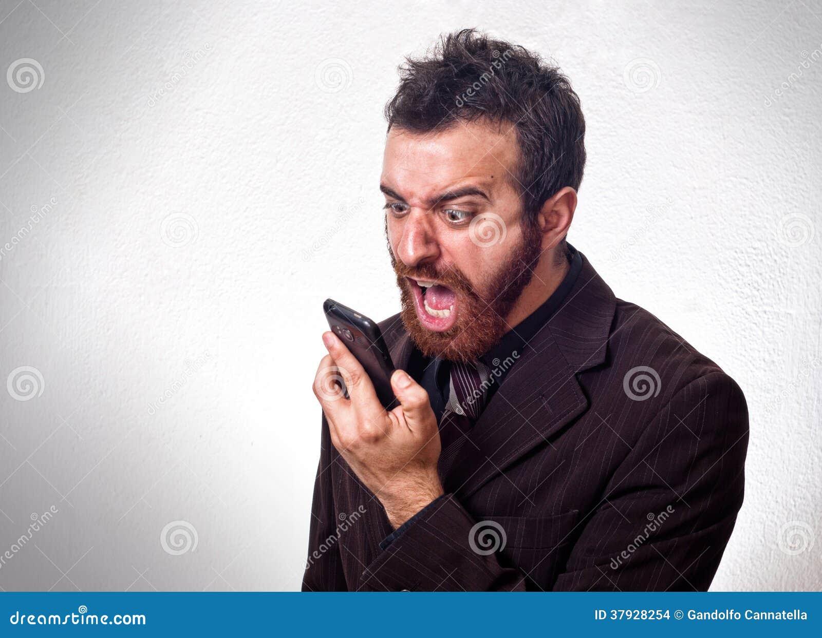 Человек в деловом костюме крича в его мобильный телефон