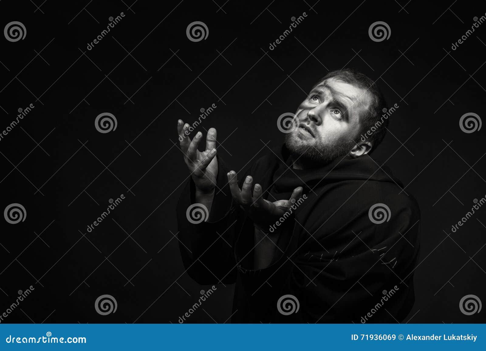 Человек в изображении монаха на темной предпосылке