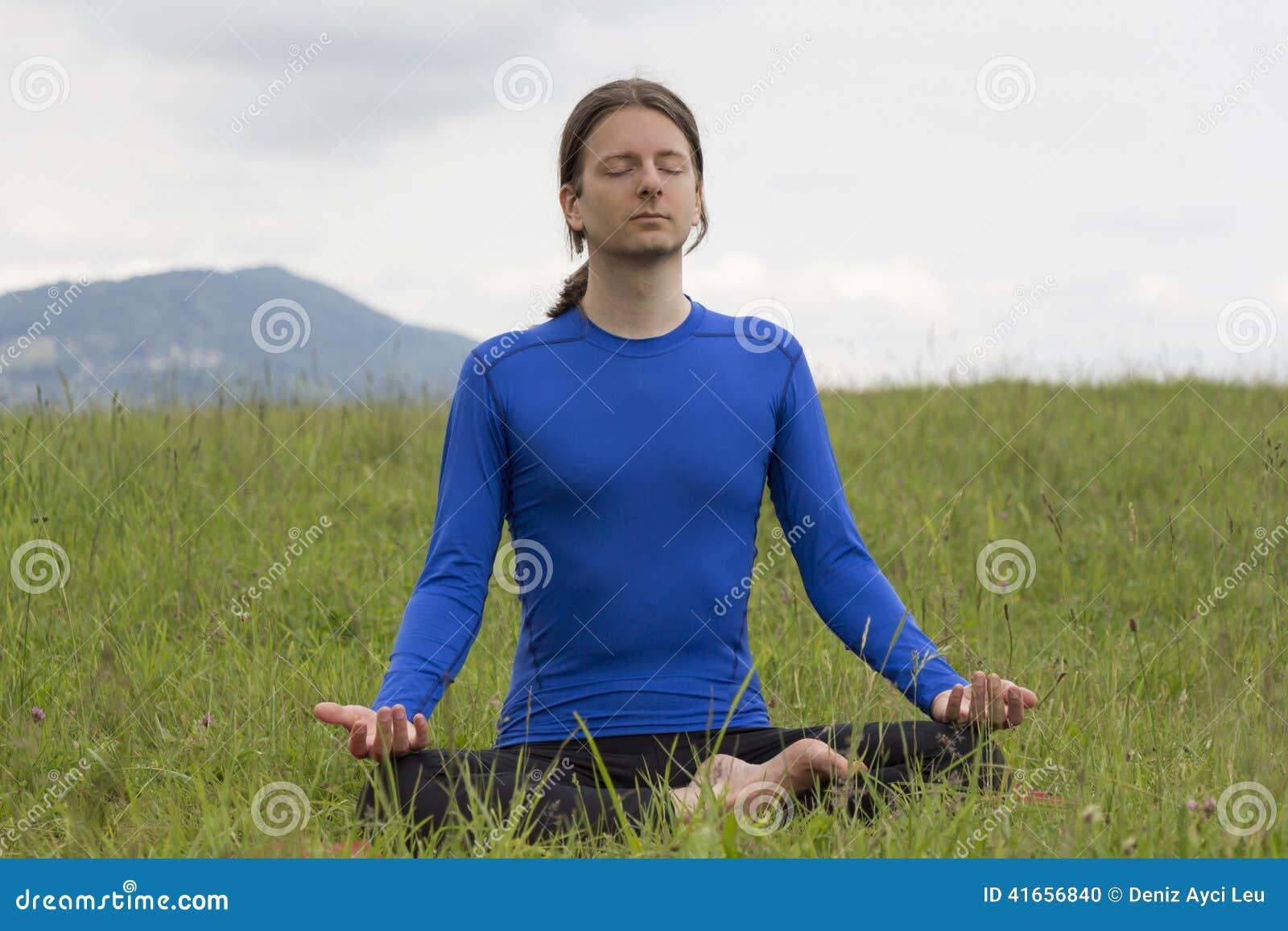 Человек в представлении лотоса размышляя во время йоги outdoors