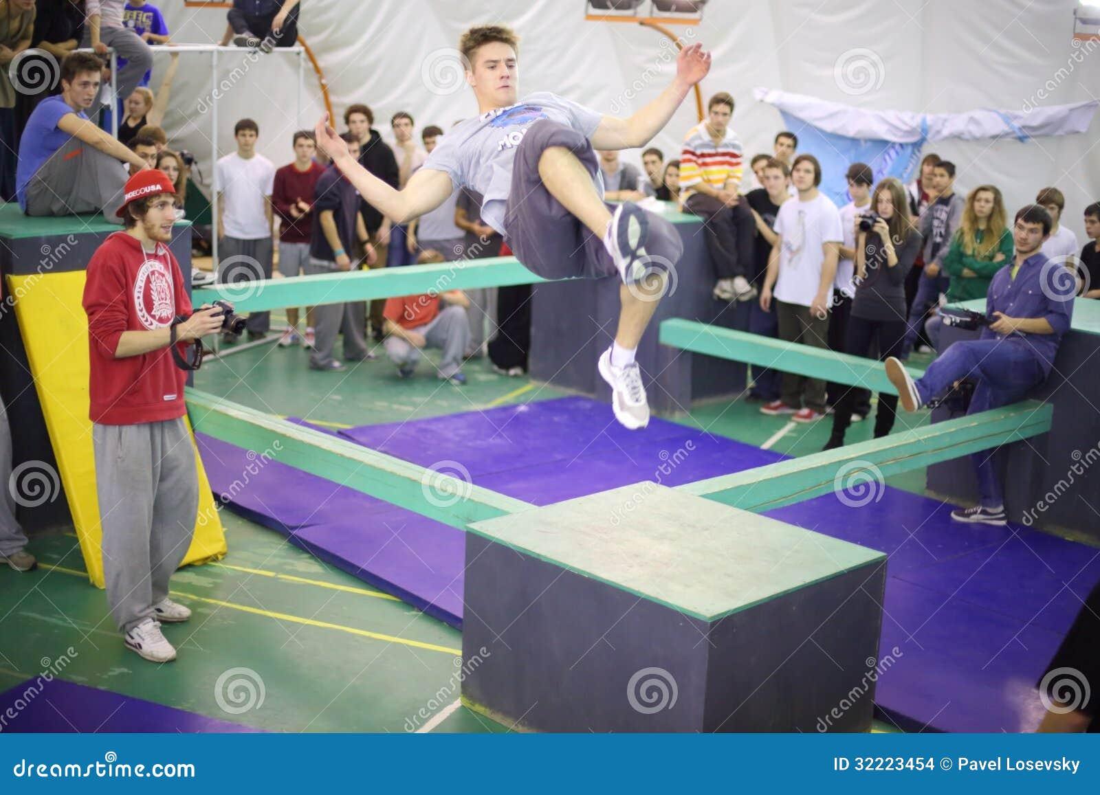 Человек в скачке на 5-ом состязании parkour, который нужно двинуть