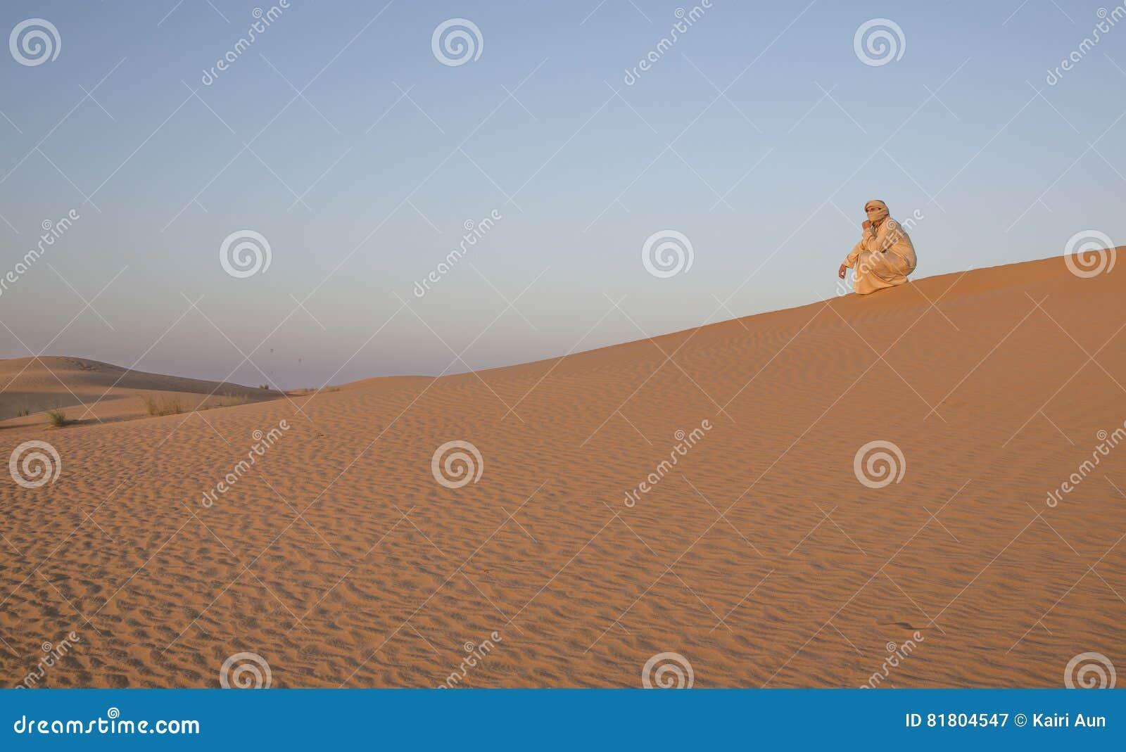 Человек в традиционном обмундировании в пустыне около Дубай