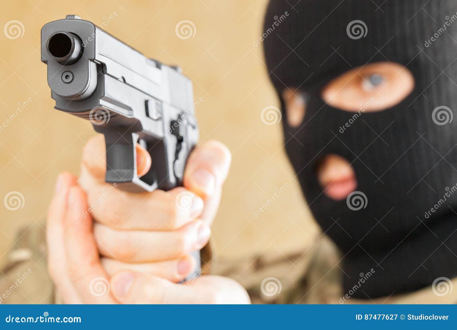 Человек в черной маске держа оружие перед им