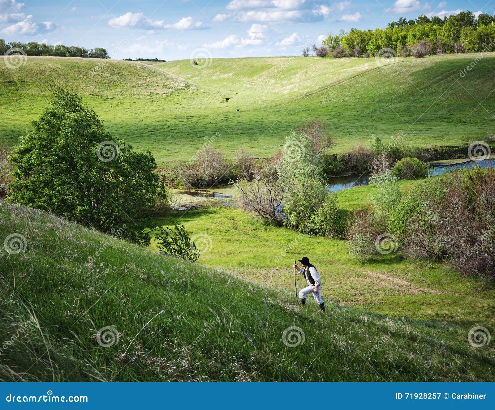 Человек в черной шляпе с stic подъемы наклон на холм