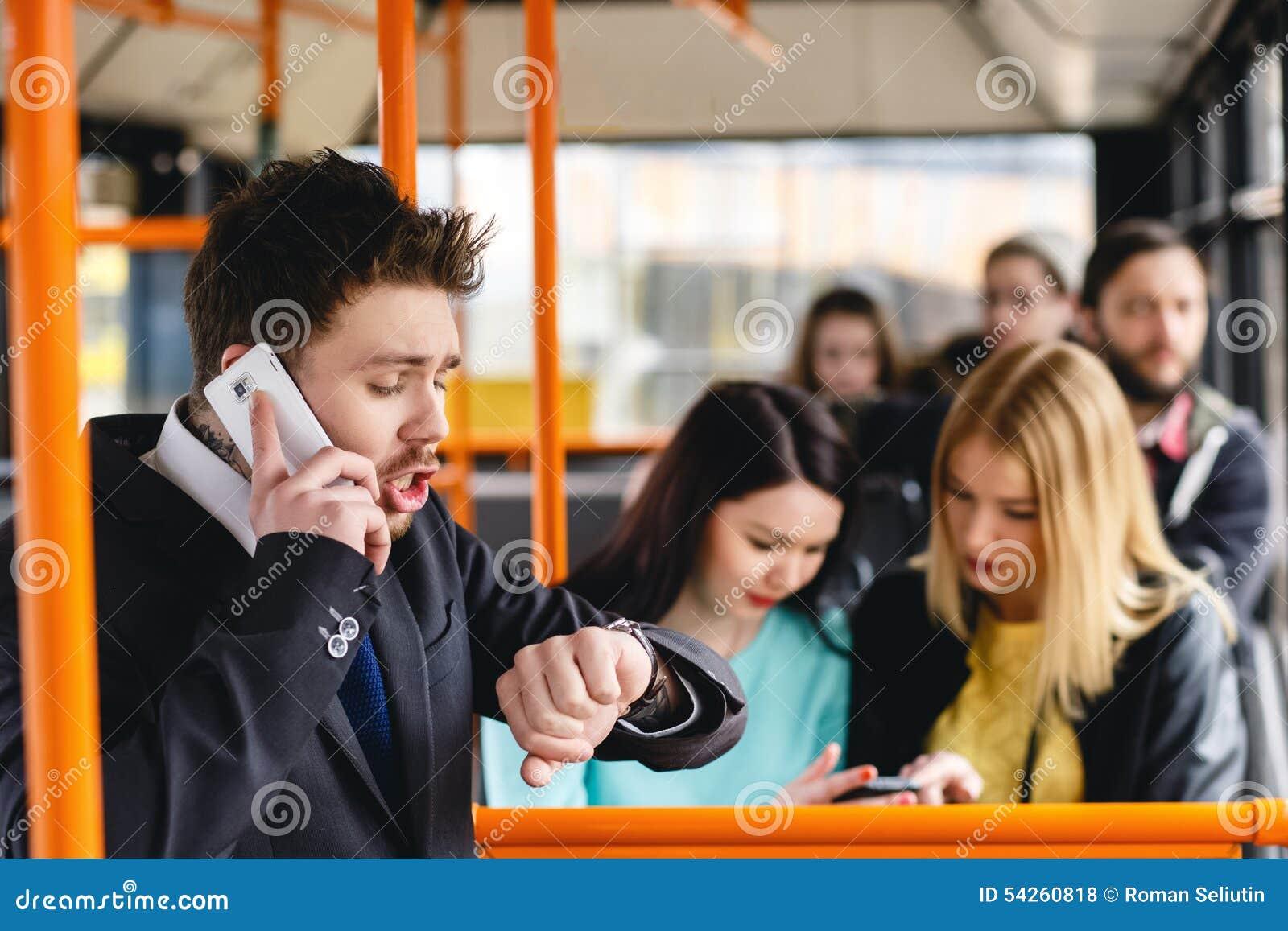 Человек говоря на сотовом телефоне, общественном местном транспорте