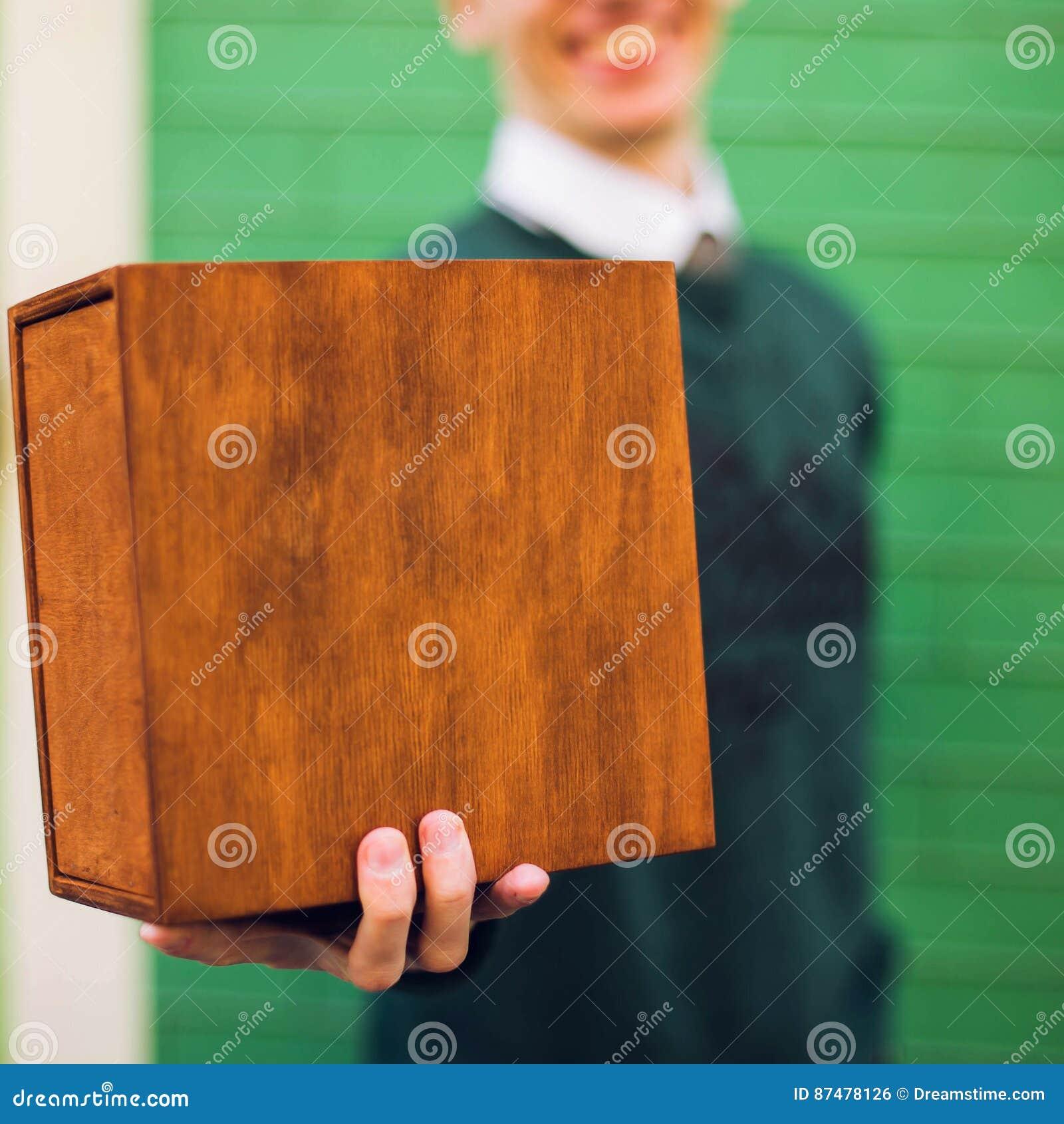 Человек держа деревянную коробку