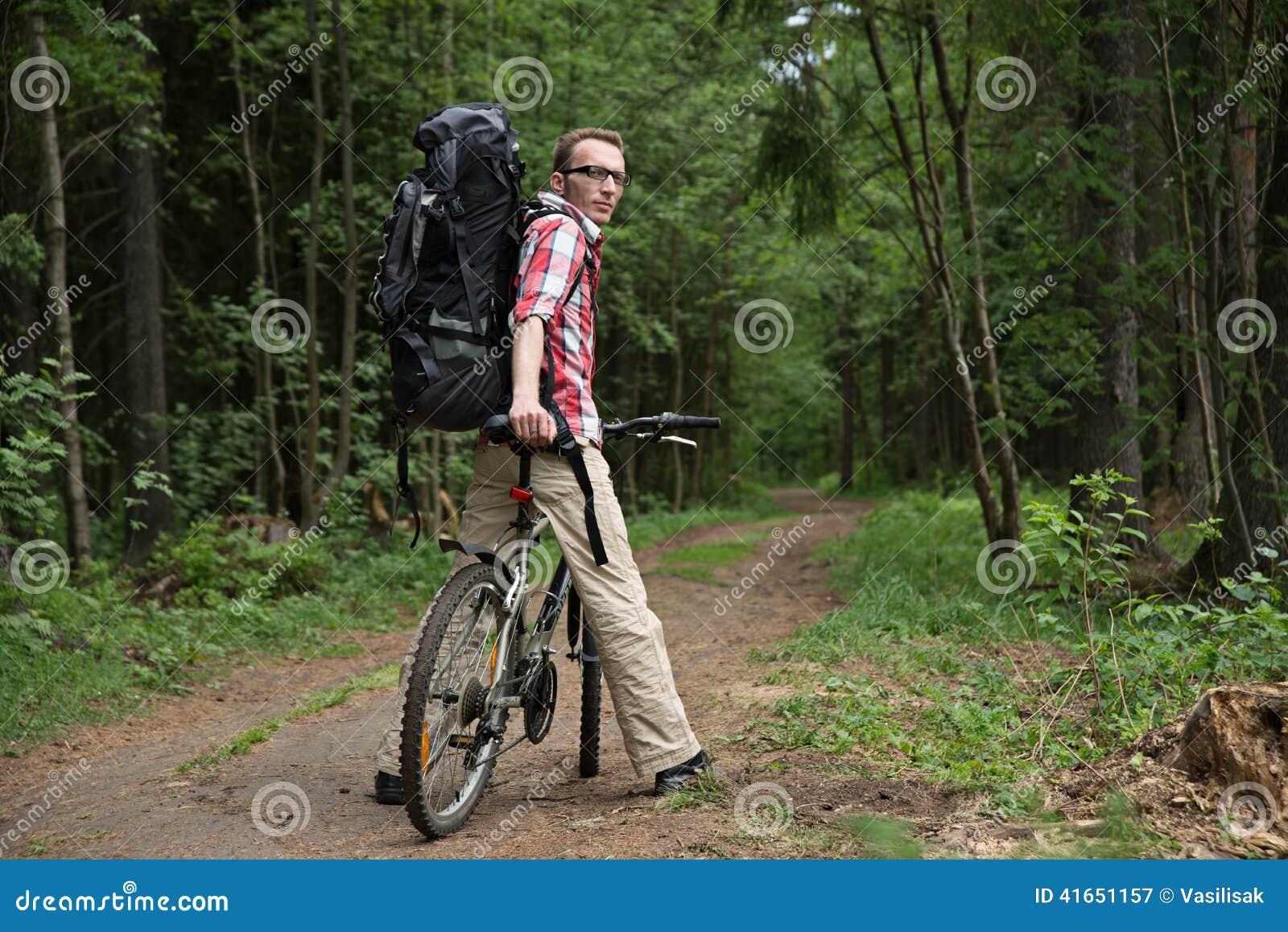 Человек, ждать друзья на проселочной дороге в лесе