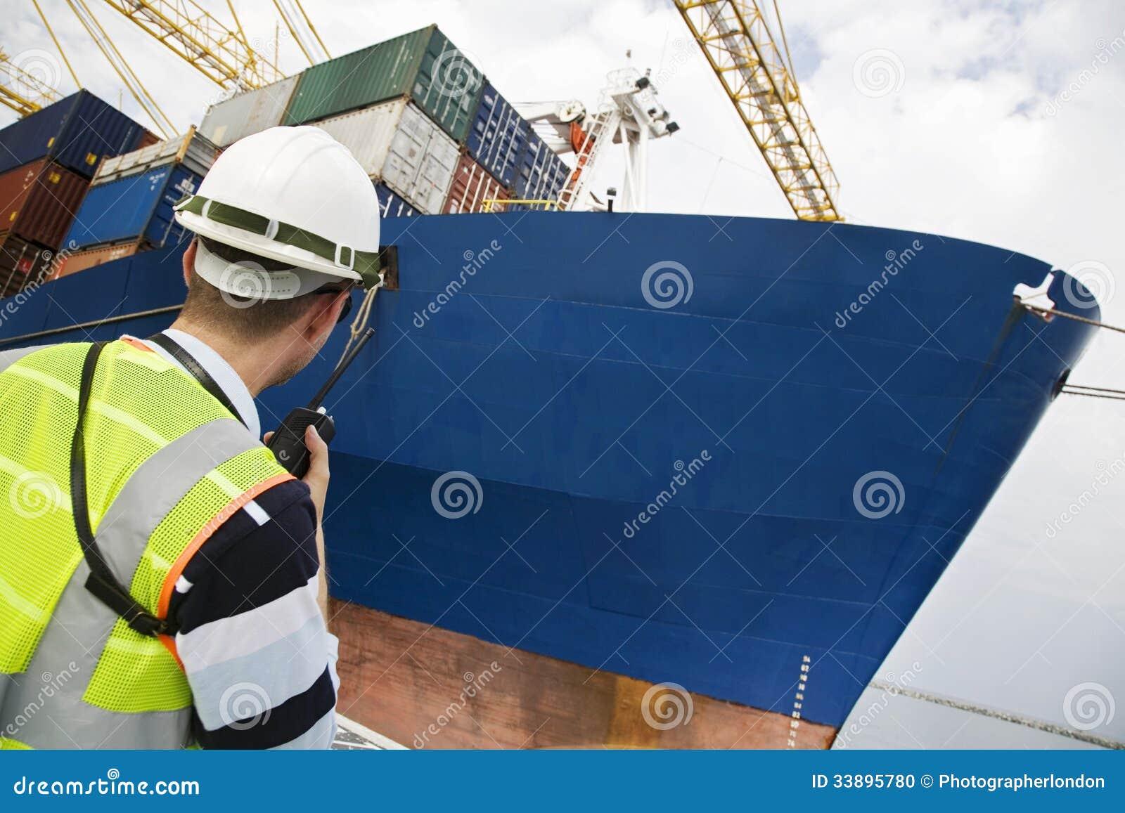 Человек используя звуковое кино Walkie на контейнерном терминале