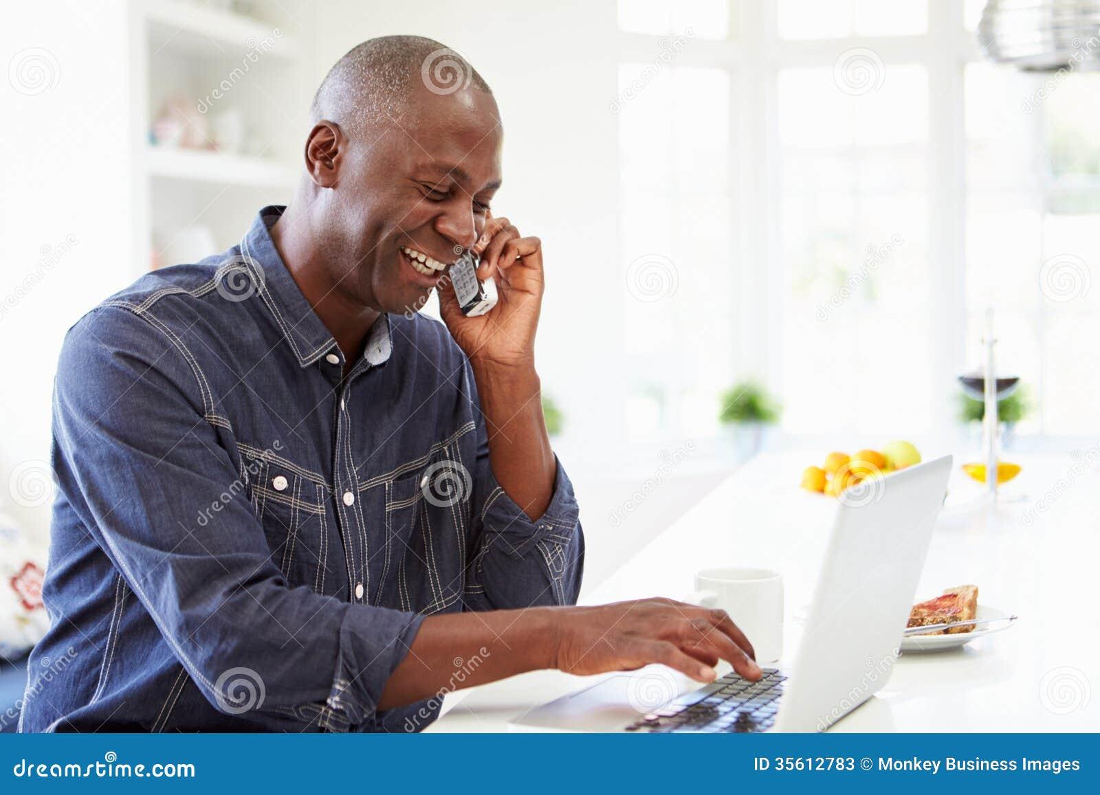 Человек используя компьтер-книжку и говорящ на телефоне в кухне дома