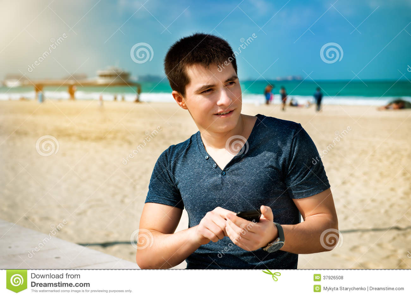 Человек используя smartphone сидя на пляже города