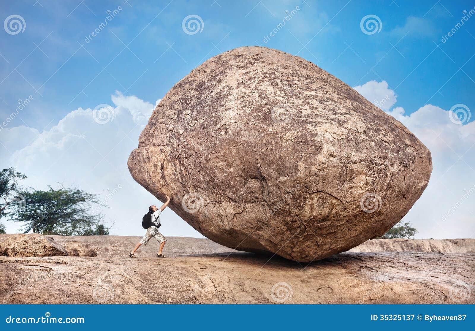 Человек нажимая большой камень