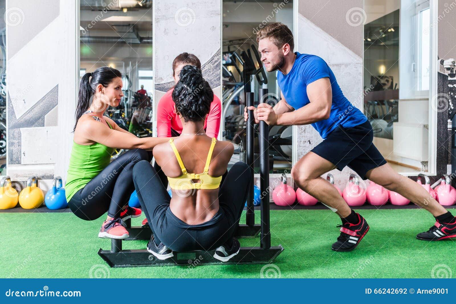 Человек нажимая женщин на тележке как тренировка фитнеса