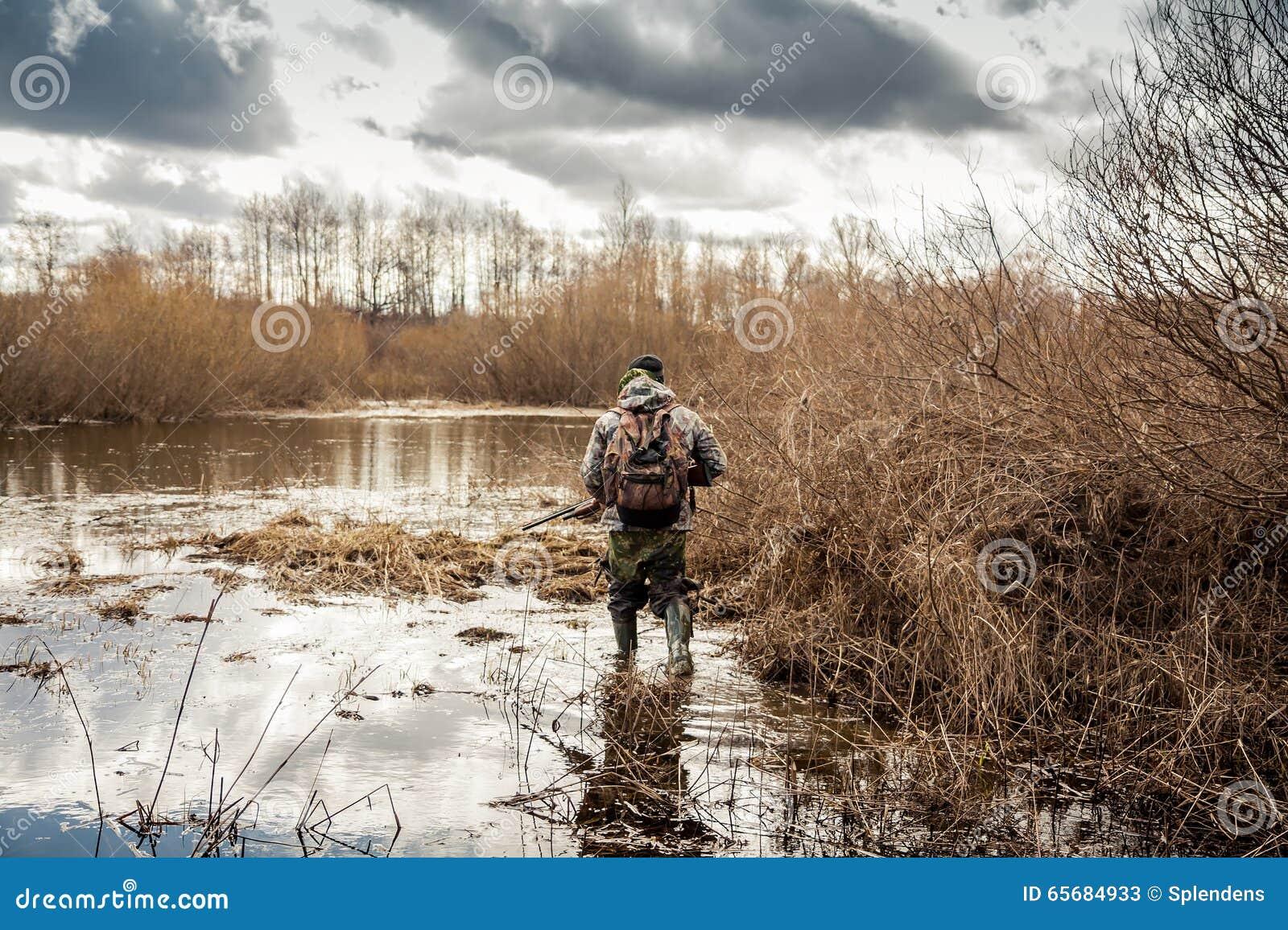 Человек охотника проползая в болоте во время периода звероловства