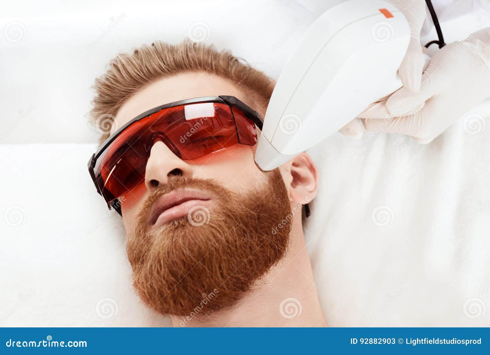 Человек получая заботу кожи лазера на стороне здоровая концепция человека образа жизни