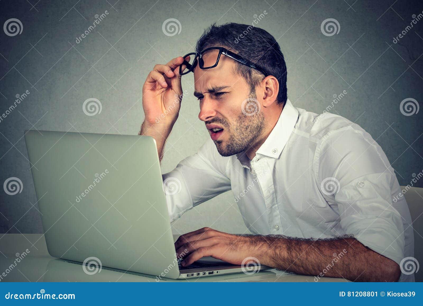 Человек при стекла имея проблемы зрения смущенные с програмным обеспечением компьтер-книжки