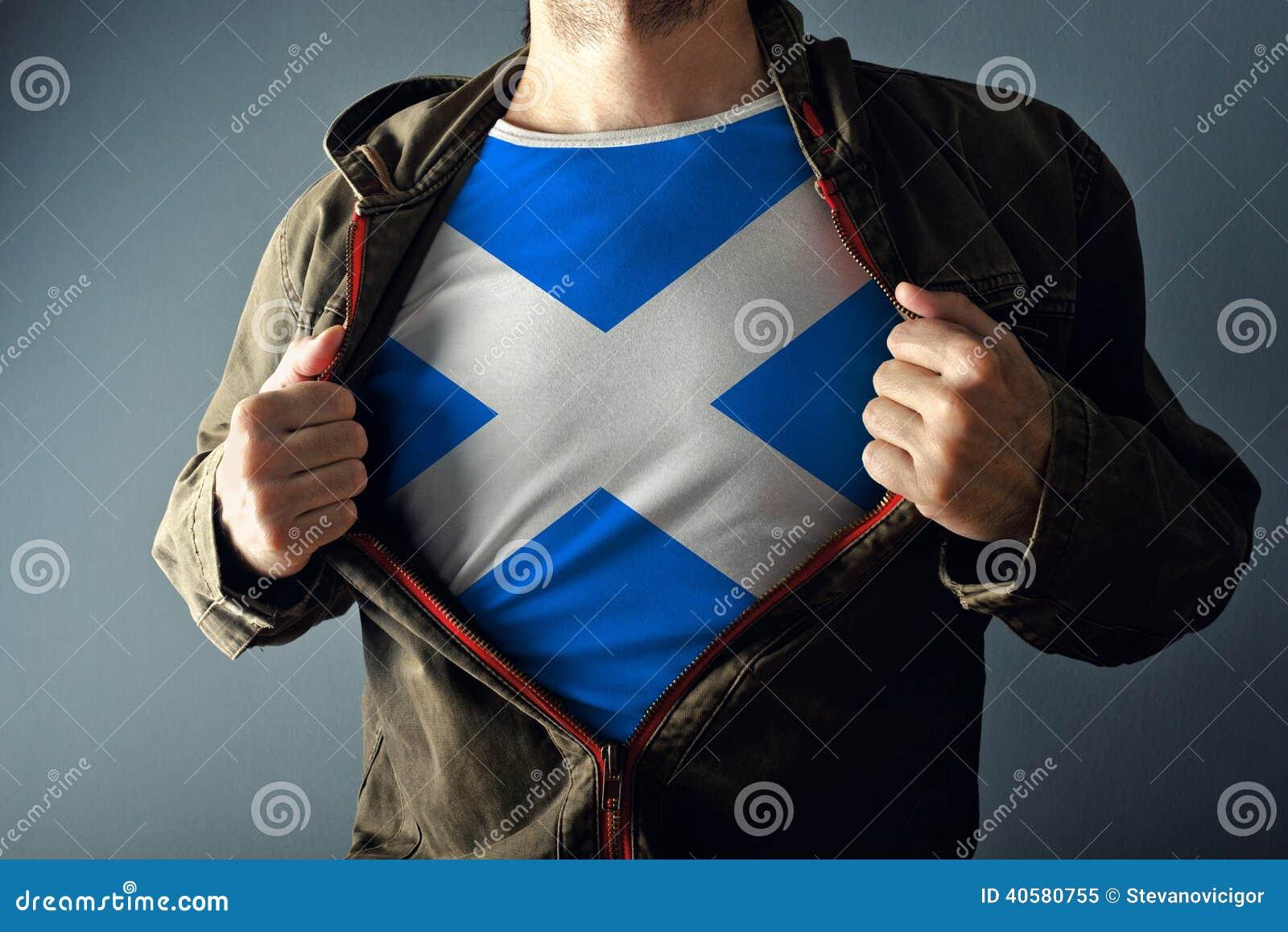 Человек протягивая куртку для того чтобы показать рубашку с флагом Шотландии