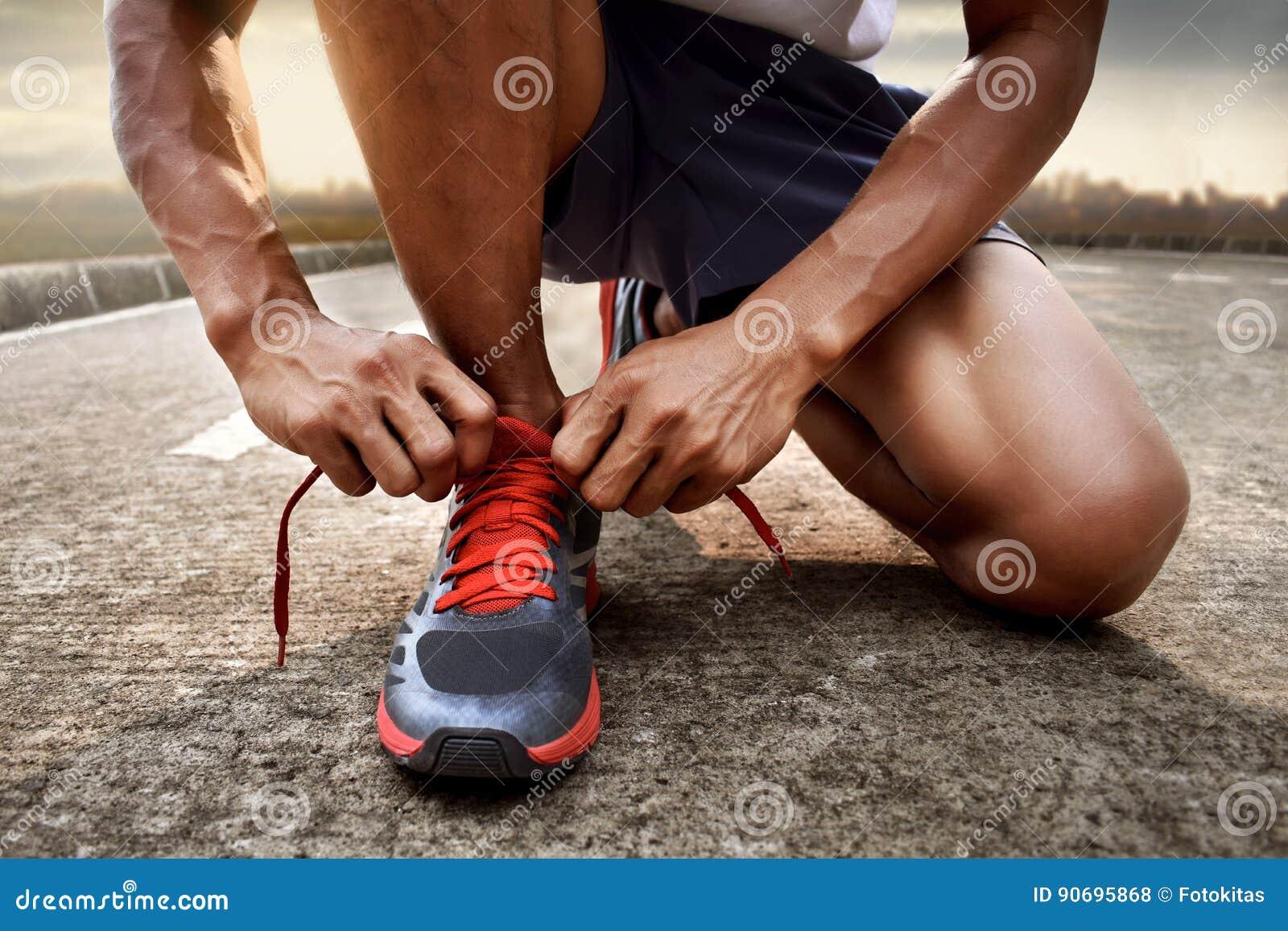 Человек связывая идущие ботинки